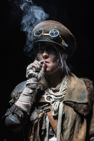 doomsday: Nuclear post apocalypse life after doomsday concept. Grimy female survivor smoking. Studio closeup portrait on white background