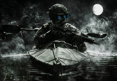 Two special forces operators with night vision goggles paddling in the army kayak in the jungle. Cloudy night, full moon, damp Stock Photo
