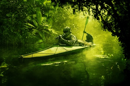 Two special forces operators paddling in the military kayak in the jungle without drawing attention. Diversionary operation ahead