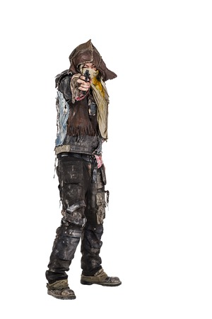 tattered: Nuclear post apocalypse life after doomsday concept. Grimy survivor with homemade weapons pointing a gun at the camera. Studio closeup portrait on white background