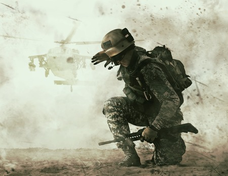 US soldier in the desert during the military operation turning to combat helicopter approaching covering his eyes. Backup is coming Banco de Imagens