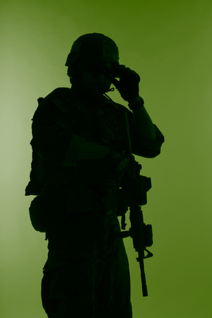 United states Marine Corps special operations command Marsoc raider with weapon. Silhouette of of Marine Special Operator green background