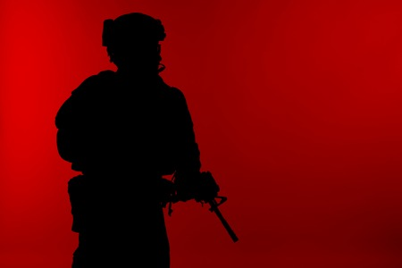 United states Marine Corps special operations command Marsoc raider with weapon. Silhouette of of Marine Special Operator red background