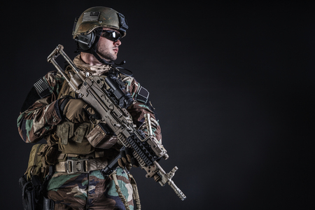 recon: United states Marine Corps special operations command Marsoc raider with weapon. Studio shot of Marine Special Operator half-turning black background