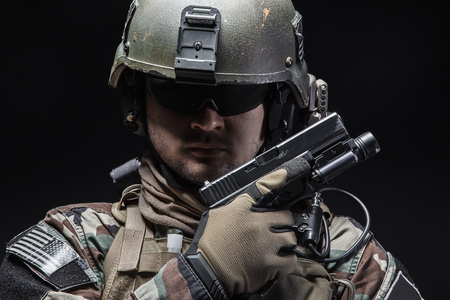 recon: United states Marine Corps special operations command Marsoc raider with pistol. Studio shot of Marine Special Operator black background