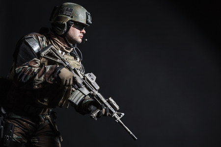 gi: United states Marine Corps special operations command Marsoc raider with weapon. Studio shot of Marine Special Operator half-turning black background