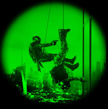 two visions: Night vision view of special forces police swat operators assault rappeling with weapons. High-rise building skyscraper. Hostage rescue concept