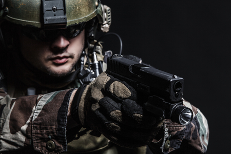 gi: United states Marine Corps special operations command Marsoc raider with pistol. Studio shot of Marine Special Operator black background