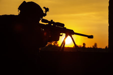 Army sniper with large-caliber sniper rifle seeking killing enemy. Silhouette on sky background. National security ensured, servicemen on guard Stock Photo