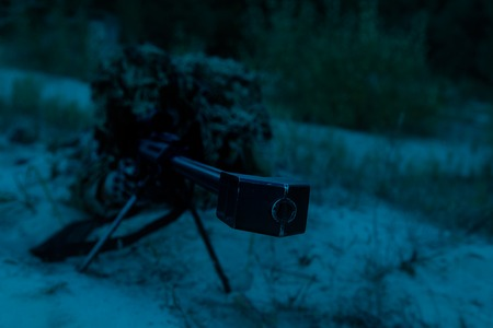 Army sniper with big rifle lying in wait in the forest at nighttime