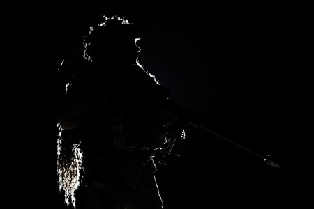 Army sniper with big rifle standing on black background. Backlit contour silhouette shot. Invisible death concept Stock Photo