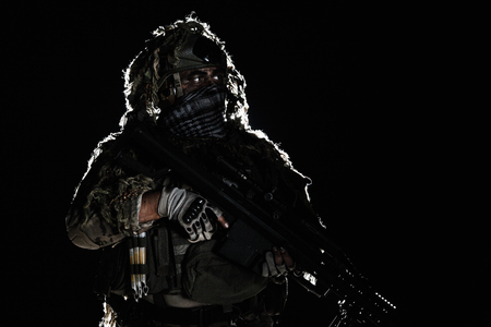 face shot: Army sniper with big rifle standing on black background. Face is painted with warpaint. Backlit contour silhouette shot