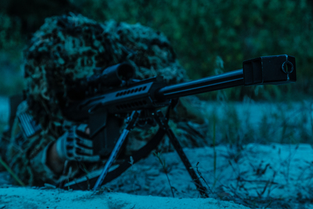 muzzle flash: Army sniper with big rifle lying in wait in the forest at nighttime