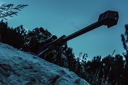Army sniper with big rifle lying in wait in the forest at nighttime. Low angle view, diagonal shot