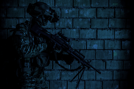 visions of america: US Army Ranger member with machinegun and night vision goggles moving along the wall during mission