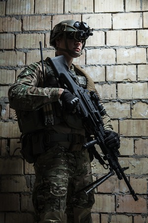 rifleman: US Army Ranger with machinegun and night vision goggles standing near the wall. Side view profile