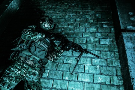 visions of america: US Army Ranger with machinegun and night vision goggles moving along the wall during mission. Low angle view