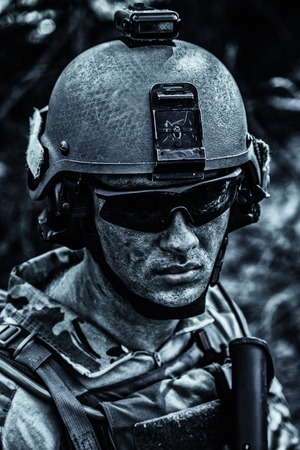 Grimy dirty and tired face of US Army Ranger, young boy wearing eyewear and combat helmet. Closeup Stock Photo