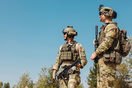 US Army Rangers with weapons in the desert. Plate carriers, eyewear goggles and combat helmets are protecting them Stock Photo