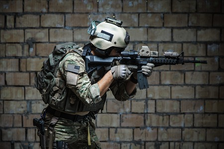 elite: US Army Ranger aiming rifle with two hands. Shooting stance and grip. Side view Stock Photo