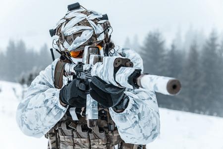 Invierno ártico montañas de la guerra. Acción en condiciones de frío. Soldado con armas en el bosque en algún lugar por encima del Círculo Polar Ártico