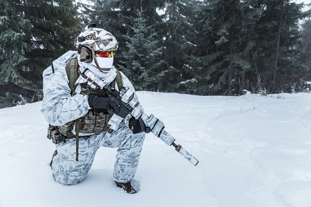 Winter arctic mountains warfare. Action in cold conditions. Trooper with weapons in forest somewhere above the Arctic Circle on one knee Stock Photo