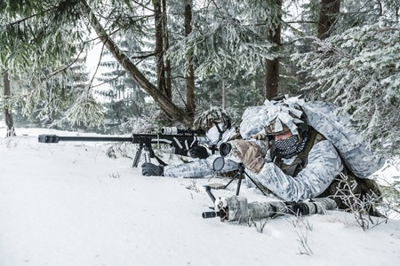 Winter arctic mountains warfare. Action in cold conditions. Sniper and spotter with weapons in wait somewhere above the Arctic circle Archivio Fotografico