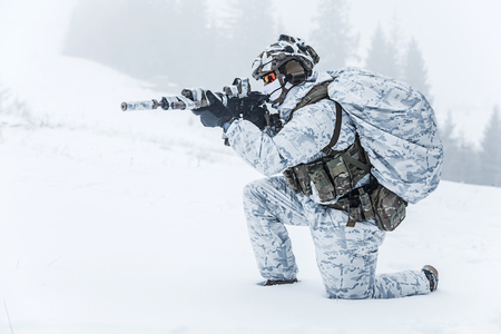 Winter arctic mountains warfare. Action in cold conditions. Trooper with weapons in forest somewhere above the Arctic Circle on the knee