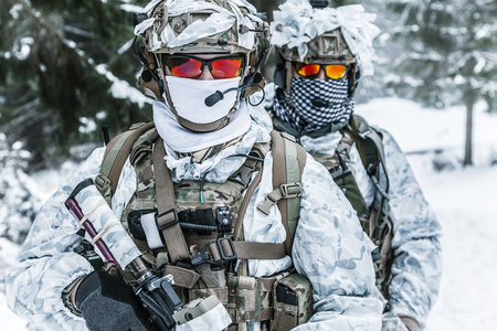 Winter arctic mountains warfare. Action in cold conditions. Soldiers with weapons in forest somewhere above the Arctic Circle Stock Photo