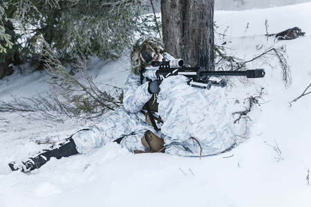 Winter arctic mountains warfare. Action in cold conditions. Sniper with weapons in forest somewhere above the Arctic Circle Reklamní fotografie