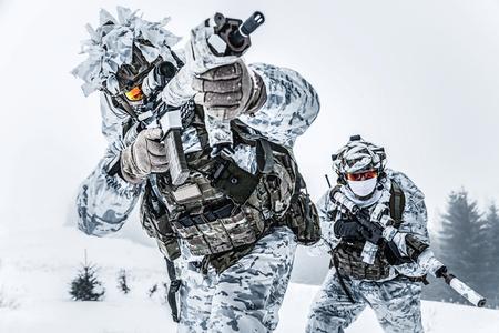 冬の山岳戦。冷たい状態でアクション。森の北極圏、低角度のビュー上にどこかの特殊部隊武器のペア 写真素材