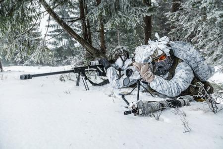 冬の山岳戦。冷たい状態でアクション。狙撃兵と偵察で武器と待つ北極圏上にどこか 写真素材