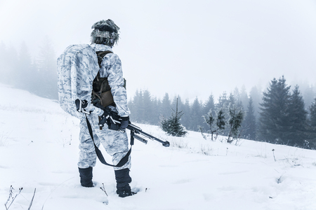 Winter arctic mountains warfare. Action in cold conditions. Sniper with weapons Stock Photo