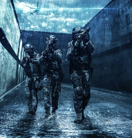 Police squad moving across sewer tunnel during mission. Police helicopter supporting from air. Raining cloudy weather, they are wet and drenched Stock Photo