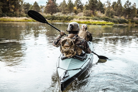 Special forces men with painted faces in camouflage uniforms paddling army kayak. Boat moving across the river, diversionary mission, back view