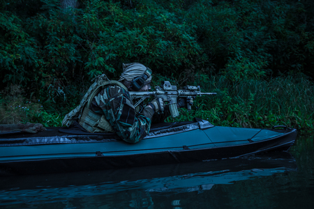 Special forces man with painted face in camouflage uniforms in army kayak. Seeking target, diversionary mission, twilight Imagens