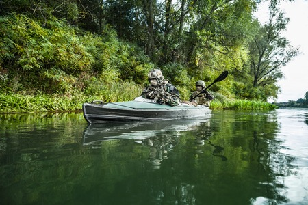sabotage: Special forces men with painted faces in camouflage uniforms paddling army kayak. Boat moving across the river, diversionary mission, diagonal view Stock Photo