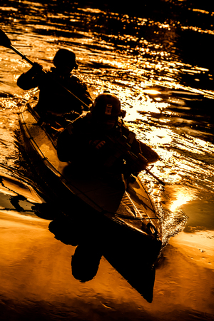 Silhouette of special forces men paddling army kayak. Boat moving calmly across the river, diversionary mission, sunset dusk