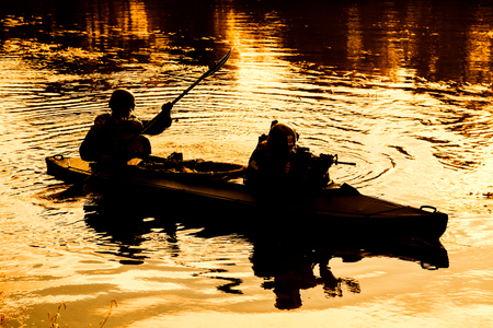 sabotage: Silhouette of special forces men paddling army kayak. Boat moving calmly across the river, diversionary mission, sunset dusk