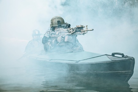 Special forces marine operators in camouflage uniforms paddling army kayak through river fog. Diversionary mission, machine gunner ahead Stock fotó