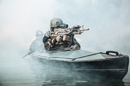 gunner: Special forces marine operators in camouflage uniforms paddling army kayak through river fog. Diversionary mission, machine gunner ahead Stock Photo