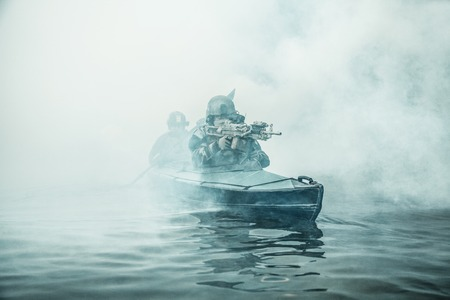Special forces marine operators in camouflage uniforms paddling army kayak through river fog. Diversionary mission, machine gunner ahead Stock Photo