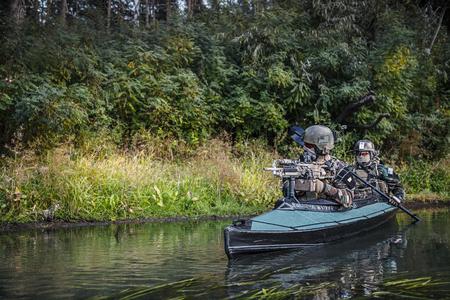 Special forces men with painted faces in camouflage uniforms paddling army kayak. Boat moving across the river, diversionary mission, copy space Imagens