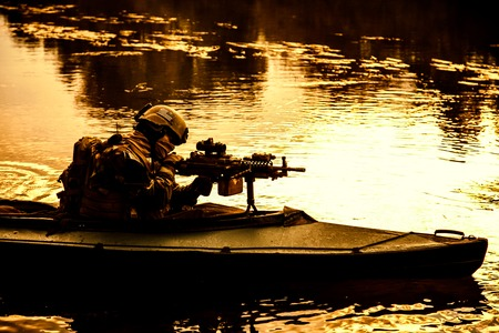 sabotage: Special forces backlit machine gunner in army kayak. Boat moving calmly across the river, diversionary mission, sunset dusk