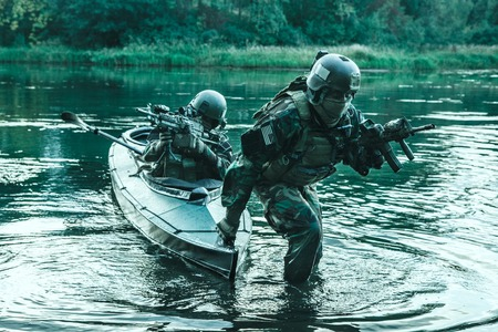 sabotage: Covert landing. Pair of armed operators with painted faces disembarking river coast from military kayak . Diversionary mission under cover of darkness