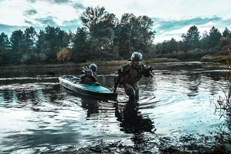 Covert landing. Pair of armed operators with painted faces disembarking river coast from military kayak . Diversionary mission under cover of darkness