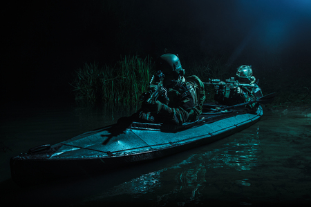 Two special forces soldiers in the military kayak. Diversionary mission under cover of darkness Stock Photo