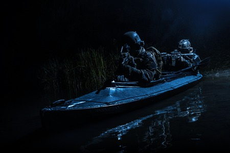 Two special forces soldiers in the military kayak. Diversionary mission under cover of darkness Imagens