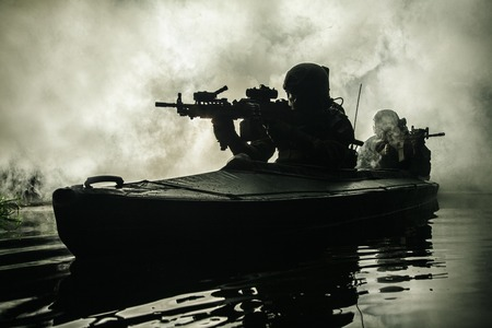 Backlit silhouette of special forces marine operators in military kayak on fire explosion background. Battle operation, bombs exploding