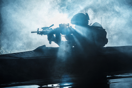 Von hinten beleuchtetes Schattenbild von Marineanbietern der speziellen Kräfte im Militärkajak auf Feuerexplosionshintergrund. Kampfoperation Standard-Bild - 74338773